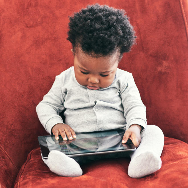 Baby sits in chair while playing on iPad