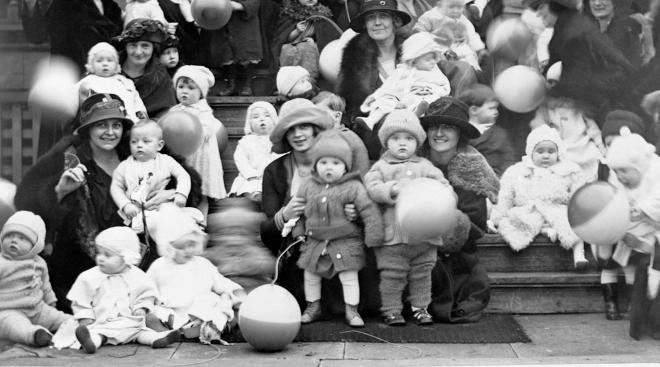 babies and moms posing on stoop for better baby contest in 1920s