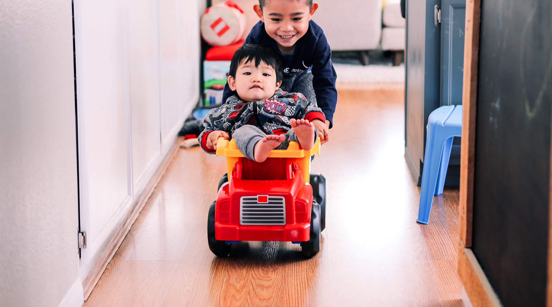two happy friends, one pushing the other in toy fire truck