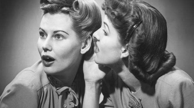 retro black and white image of two women whispering