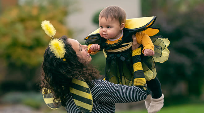 Getty mom and baby daughter in matching bumblebee Halloween costumes
