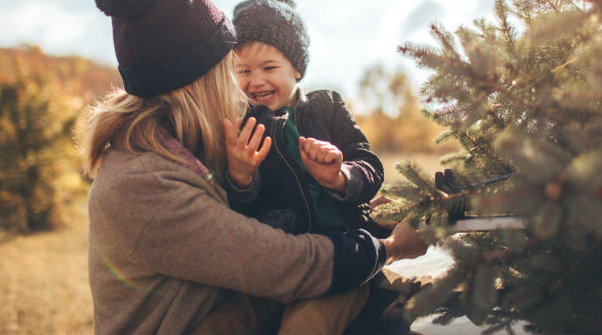 mom holding her young son while getting their christmas tree ready