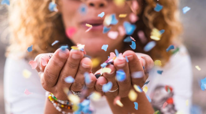 woman blowing confetti at gender reveal