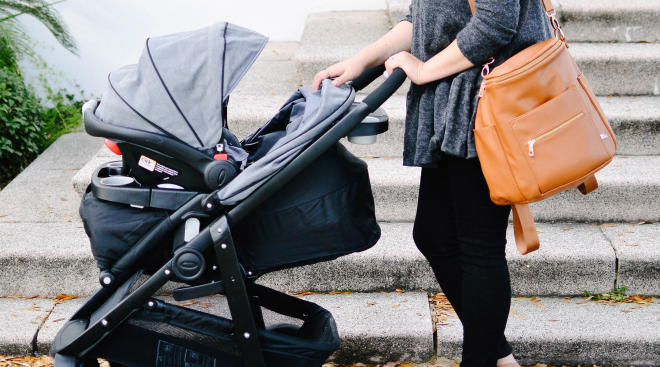 mom holding diaper bag and  walking baby in stroller