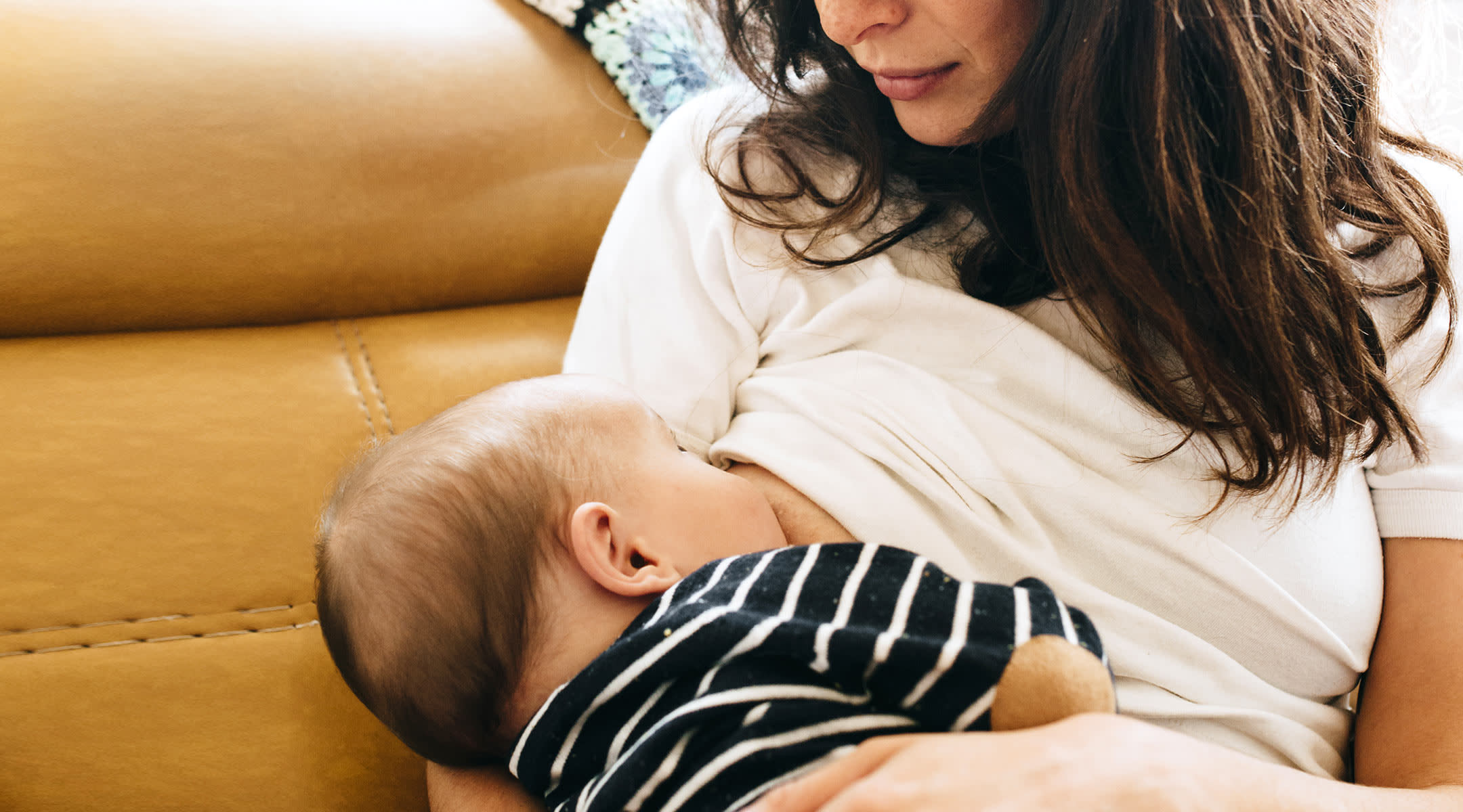 new mom breastfeeding new baby at home