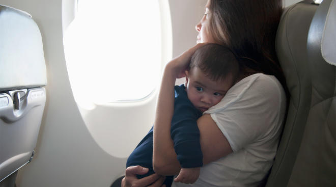 mom holding upset baby on airplane