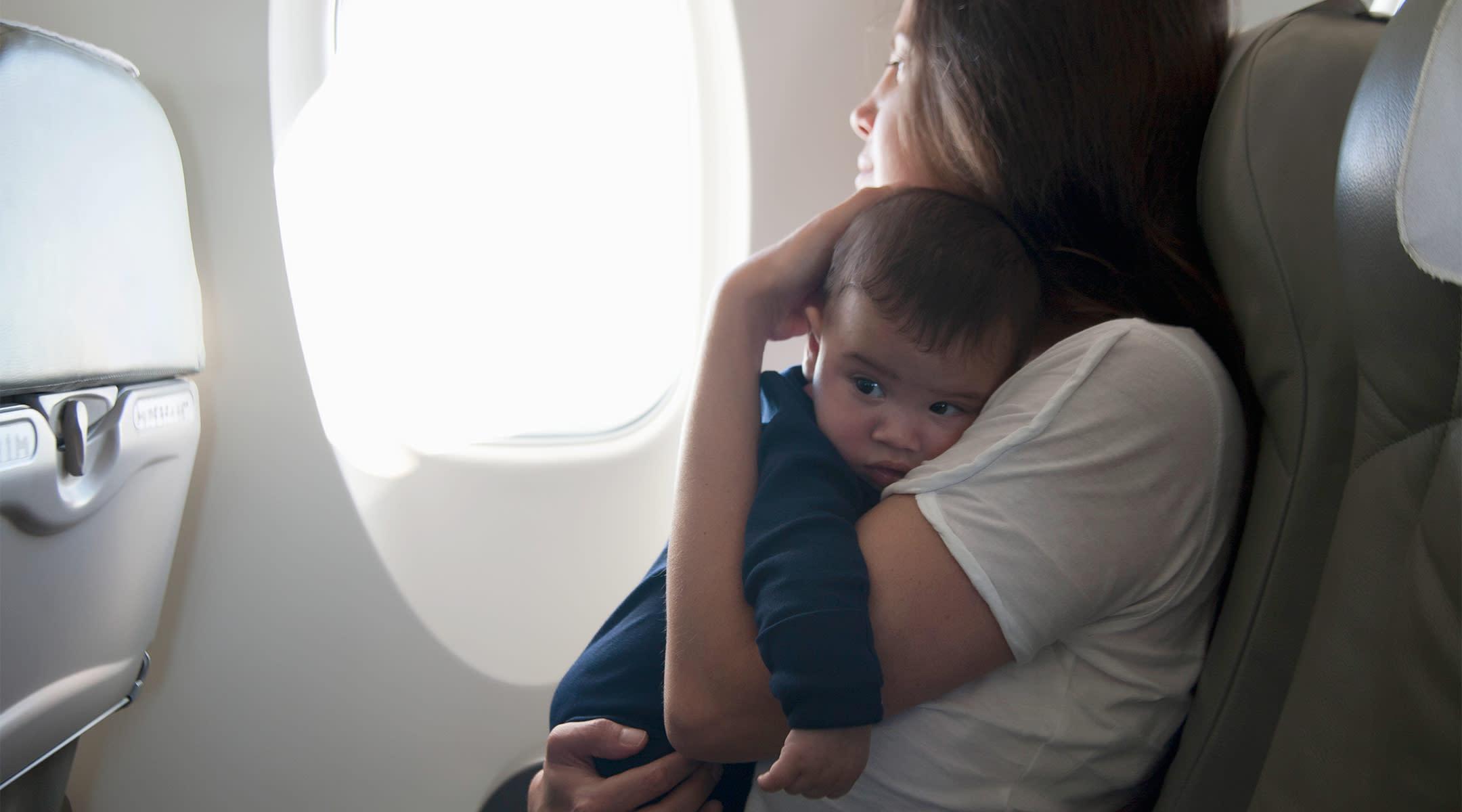 mom holding upset baby on airplane