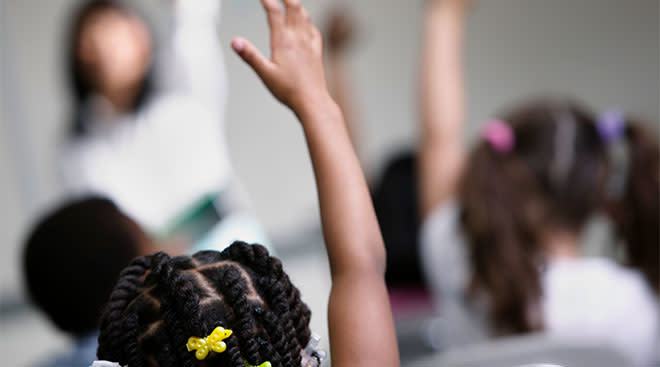 children in classroom with their hands raised