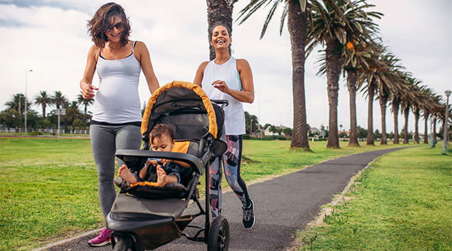 Pregnant woman and her friend walking with baby in stroller for exercise.