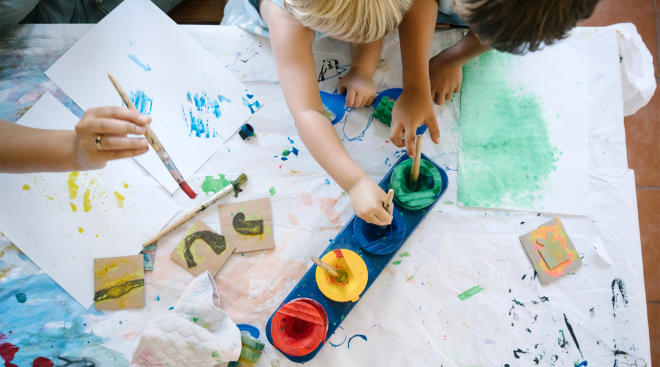 two pairs of toddler hands paint on large piece of paper