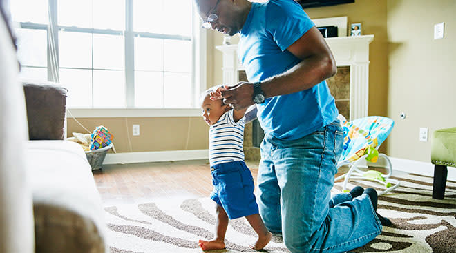 dad helping baby learn to walk in living room