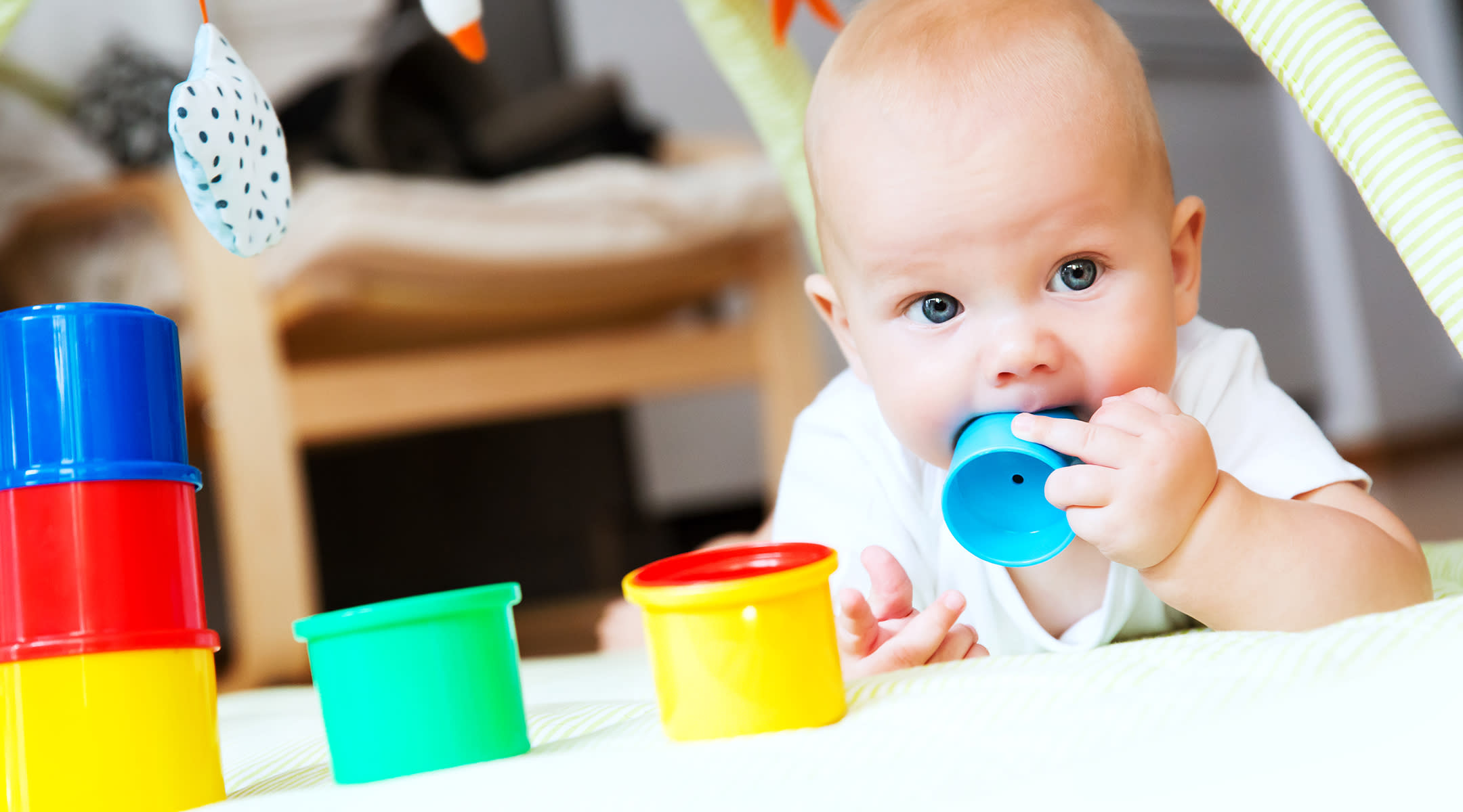 baby chewing on colorful toys