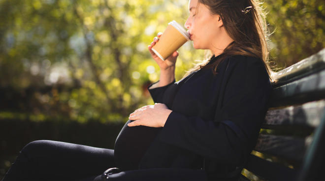 pregnant woman on a bench outside drinking coffee