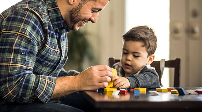 dad plays with blocks with his son at table