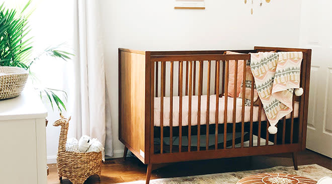 baby nursery with a medium hued wooden crib and blanket draped over the side