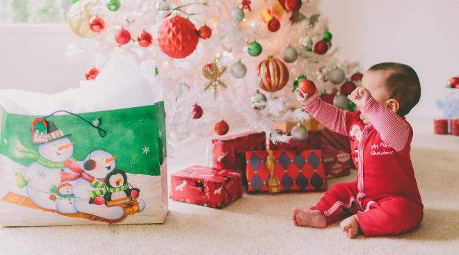 baby holding up red ornament by decorated christmas tree for his/her first christmas