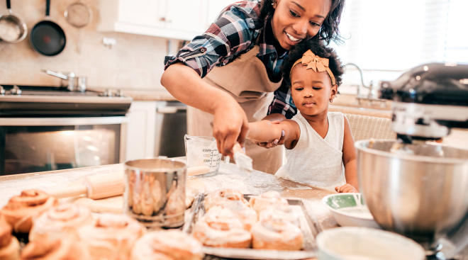 mom helping toddler bake in the kitchen
