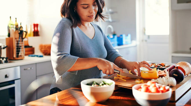 woman preparing healthy meal with vegetables in kitchen