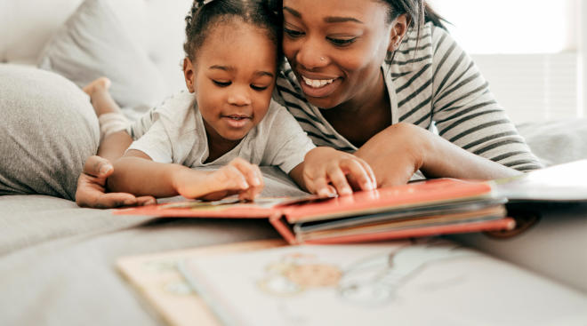mom snuggling with her daughter while reading books
