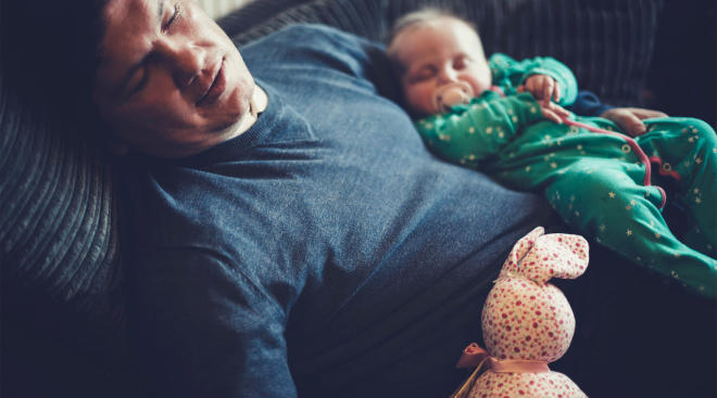 dad sleeping with baby on couch at home