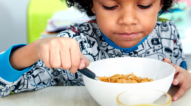 child eating his breakfast cereal