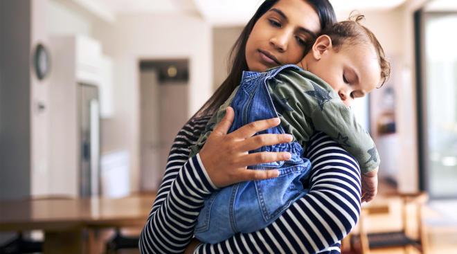 tired mom holding her toddler