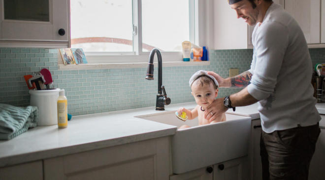 Dad giving baby a bath in the kitchen sink.