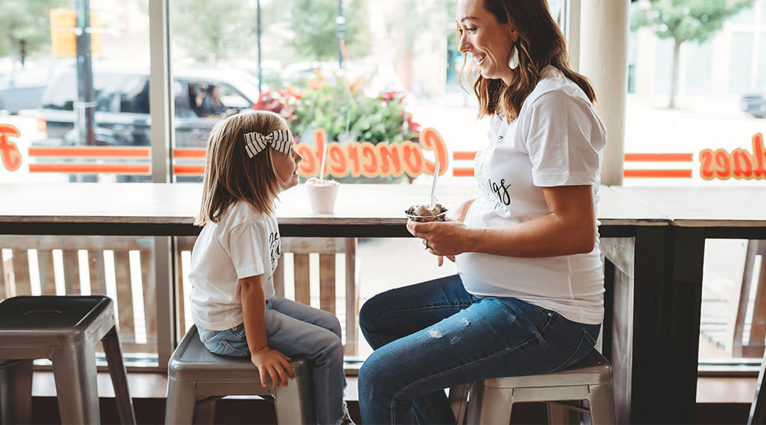 Pregnant mom sits with her young daughter eating ice cream