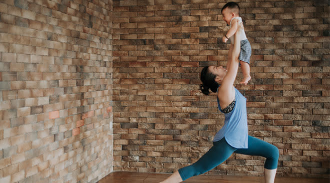 Woman exercising at home while holding her baby up.
