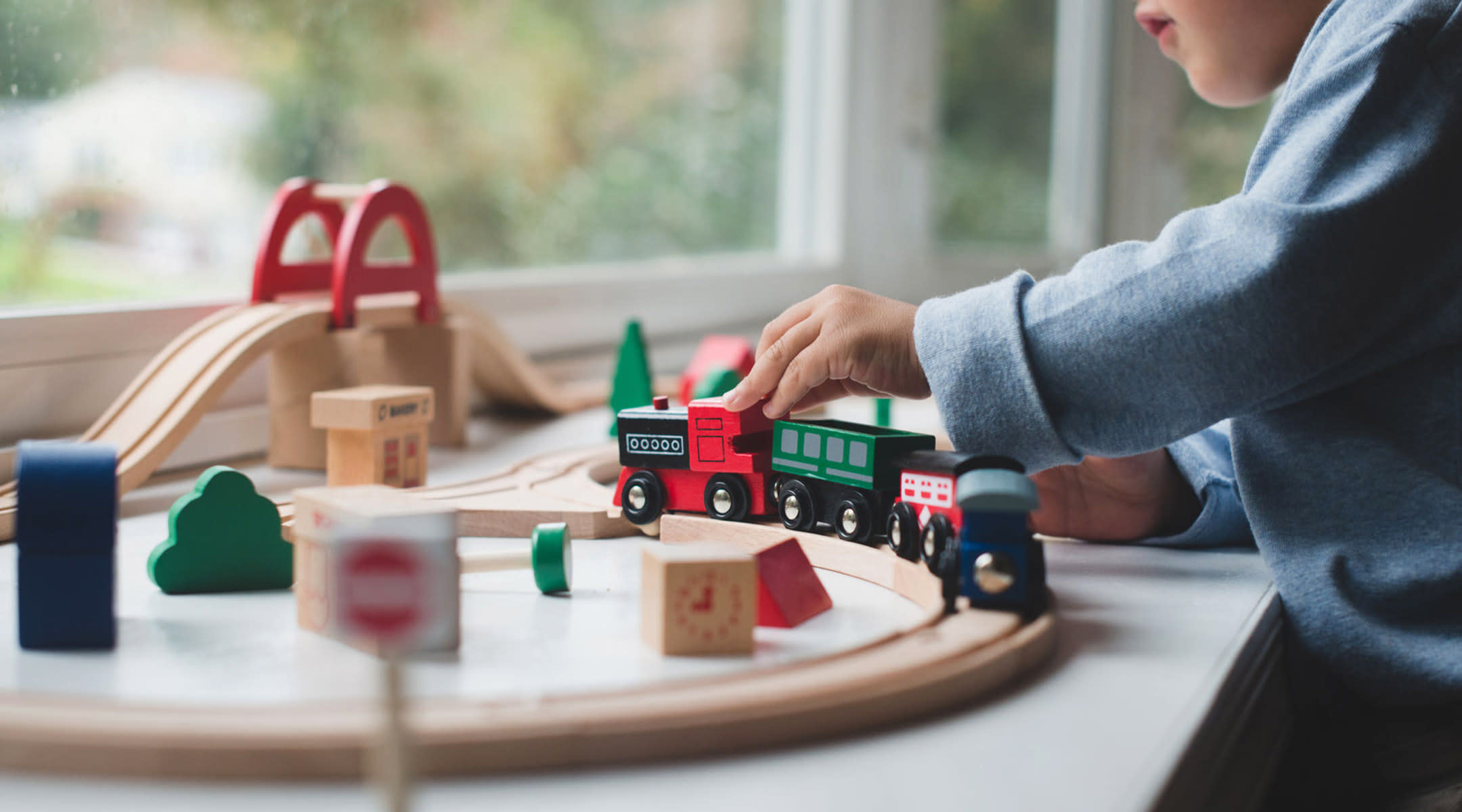 toddler plays with toy train