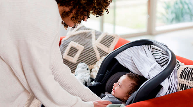 Mom strapping infant son in car seat