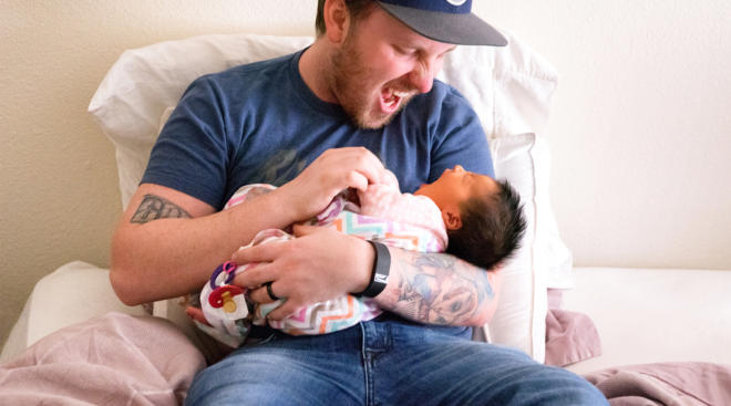 excited dad holding his newborn baby