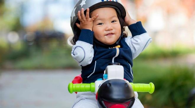 toddler holding helmet on play bike