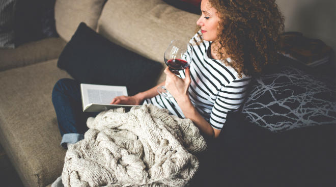 mom having alone time reading a book and drinking a glass of wine.