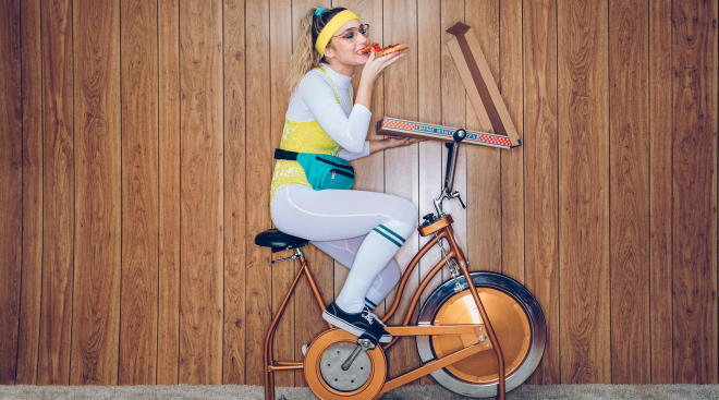 woman dressed in 1980s style on an exercise bike