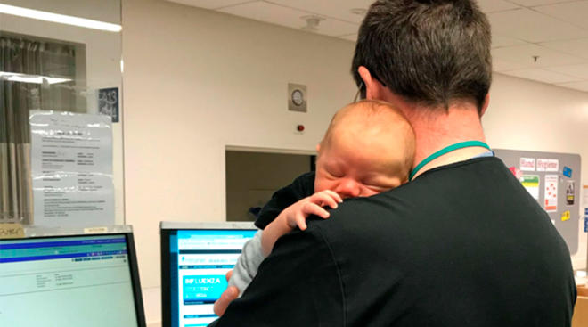 er doctor holding a sleeping baby while working in hospital
