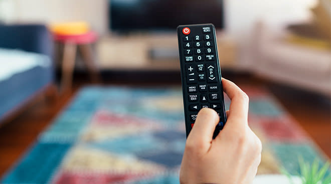 hand holding remote control with tv in the background