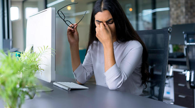 upset woman in her work office putting her head in her hands