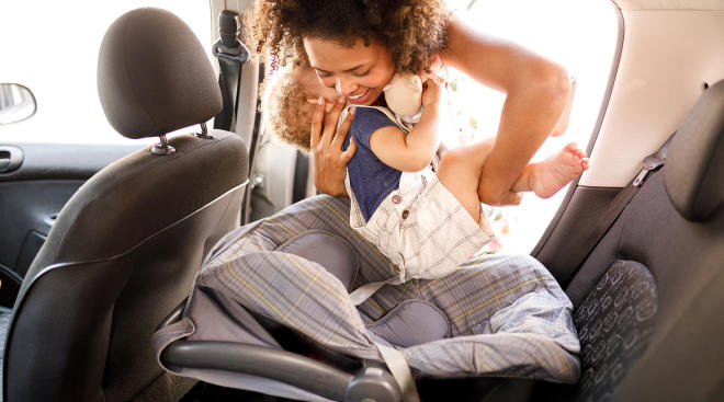 mom putting her baby in to the car seat
