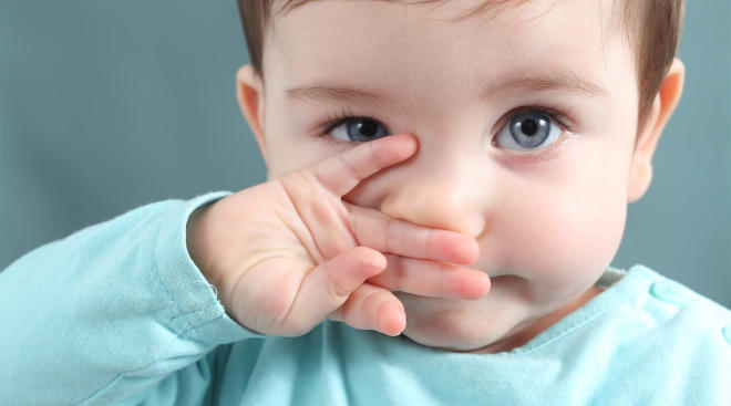toddler covering her mouth with her hand