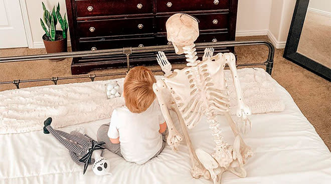 toddler boy brings halloween skeleton with him everywhere