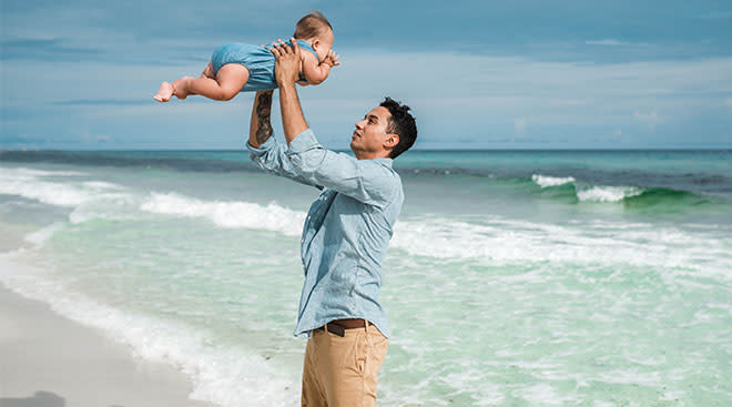 happy dad lifting his baby into the air at the beach