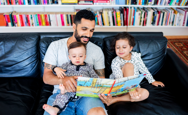 dad reading kids' book to kids in living room