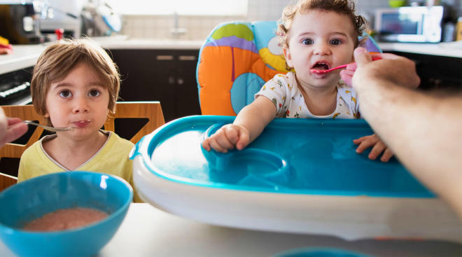 older sibling and toddler sibling sitting and eating with baby spoon
