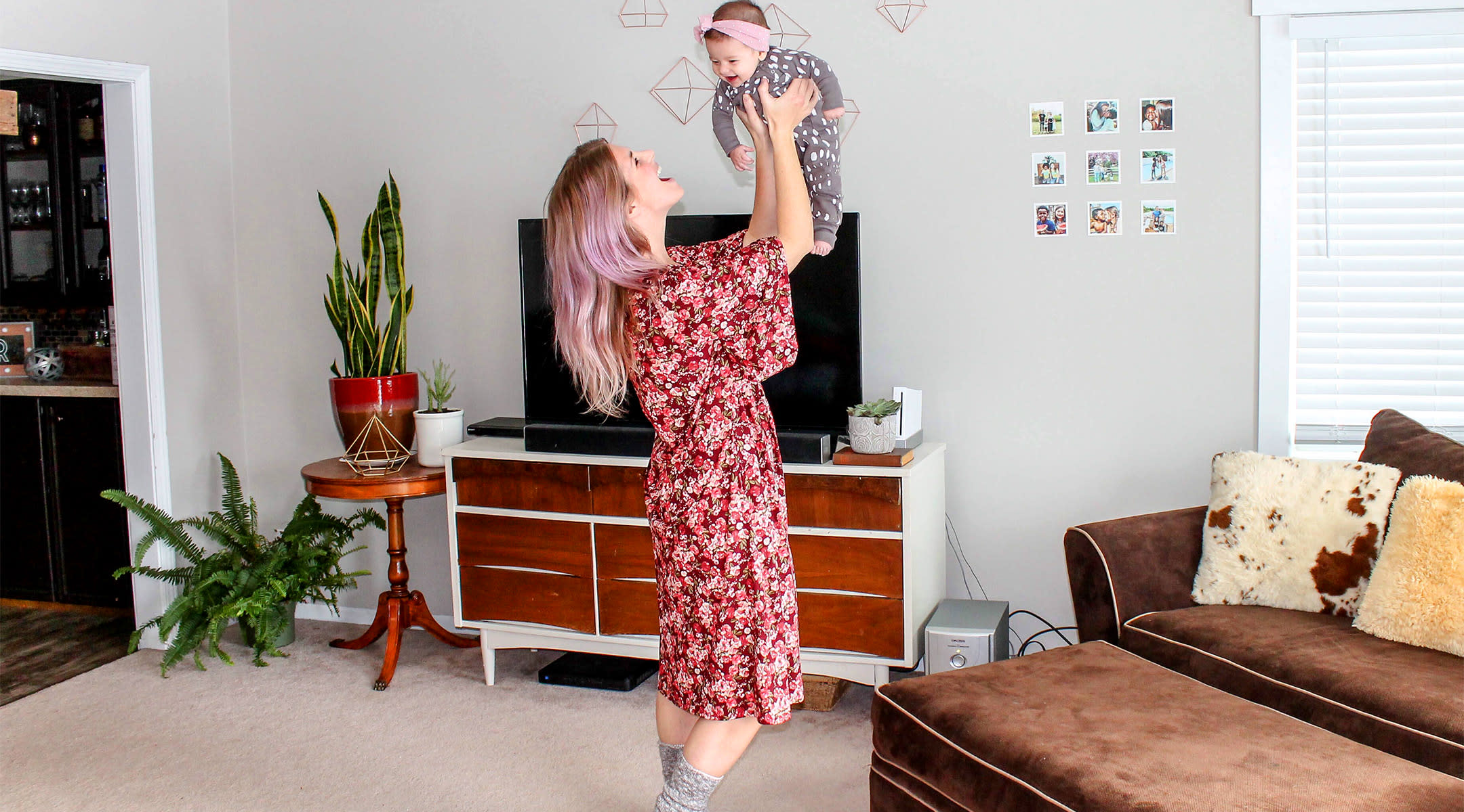 happy mom lifting up baby and singing to her