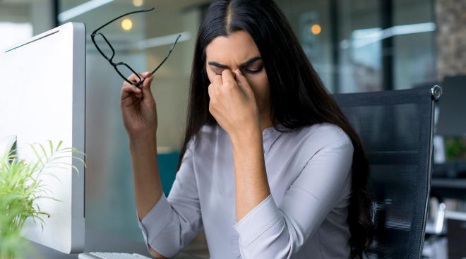 woman touching her eyes while working on computer