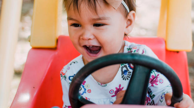 toddler happily playing in red kid car