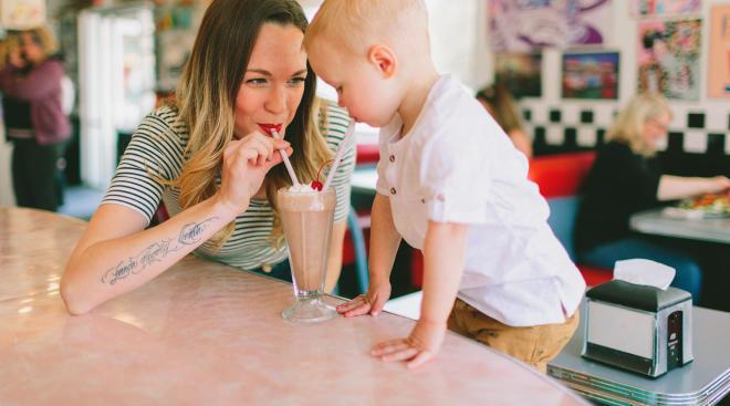 mom indulging child with chocolate milkshake demonstrating permissive parenting style