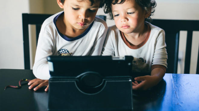 two sibling boys watching tablet device