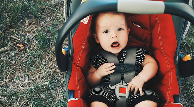 baby strapped in car seat and looking at the camera with an open mouth